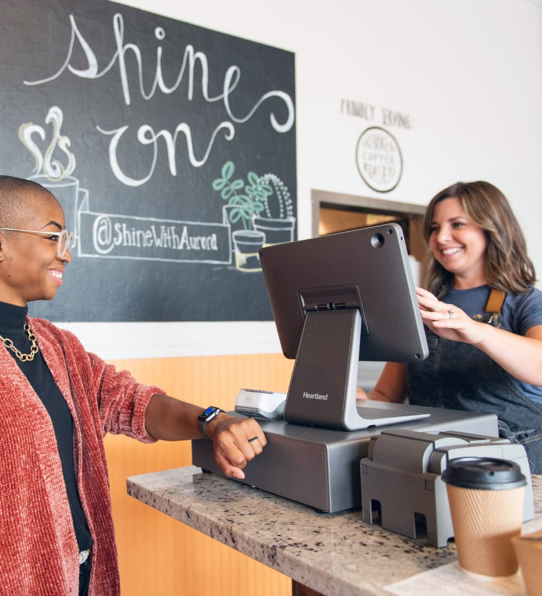 A coffee shop worker processing customer's payment