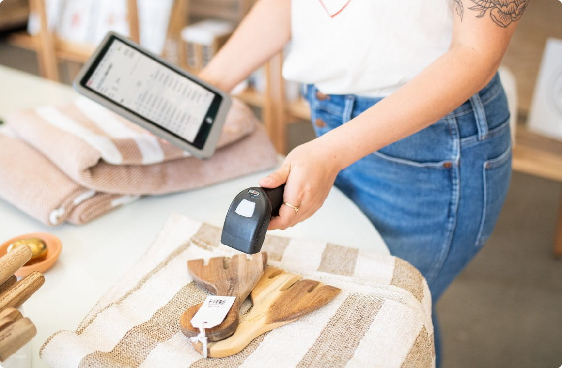 A store employee scanning merchandise with a mobile device of retail technology solutions and point of sale