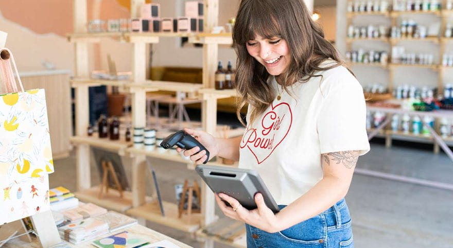 A retailer worker with mobile device scanning merchandise