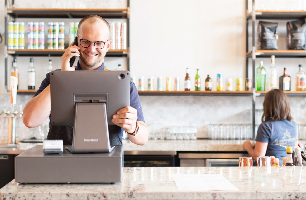 A bar worker looking at a point of sale screen while being on the phone