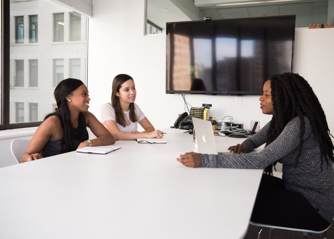 Three women in a conference room, meeting