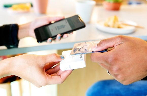 A customer making a payment via mobile point of sale hardware through a credit card