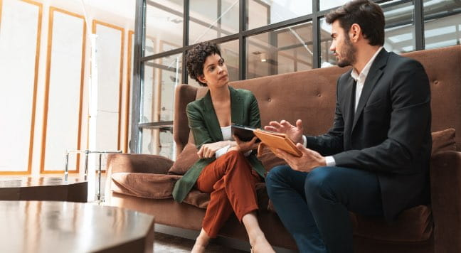 Two people meeting on a couch at an office