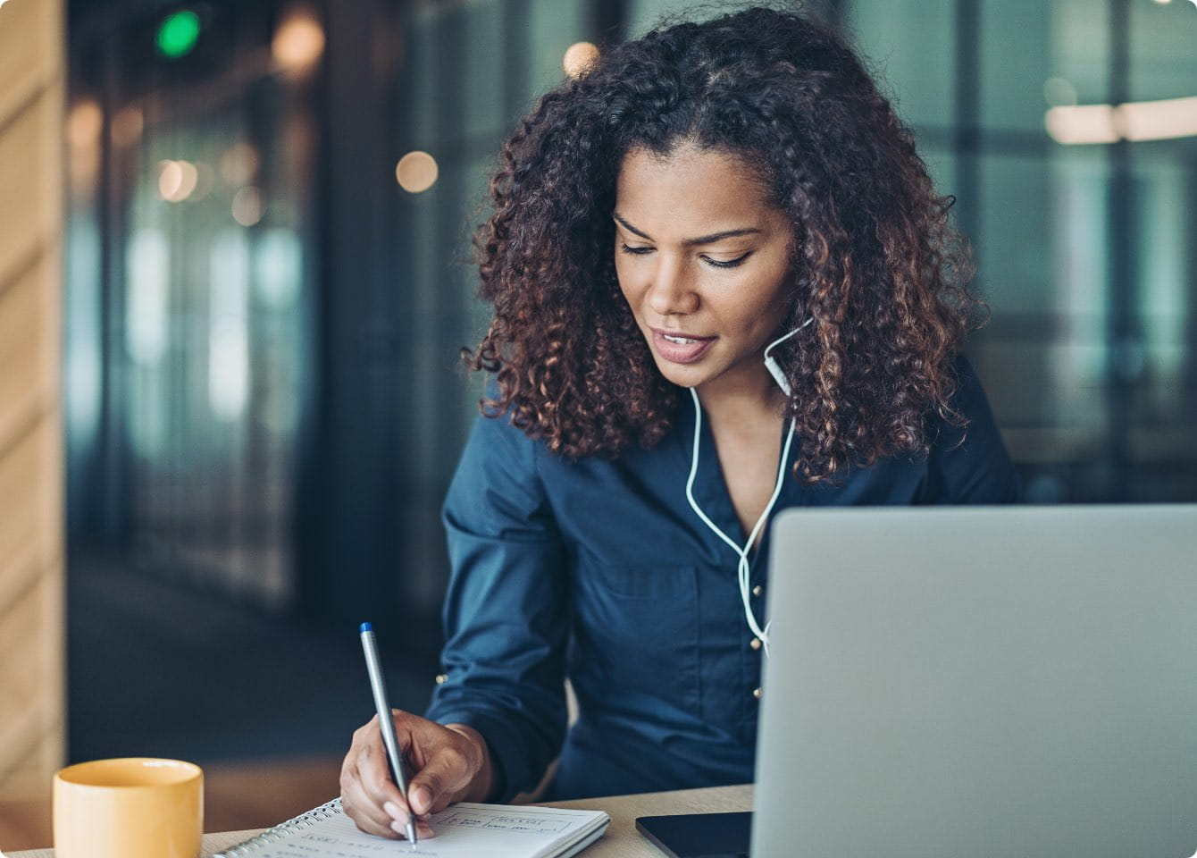 A woman with headphones working on a laptop and taking notes