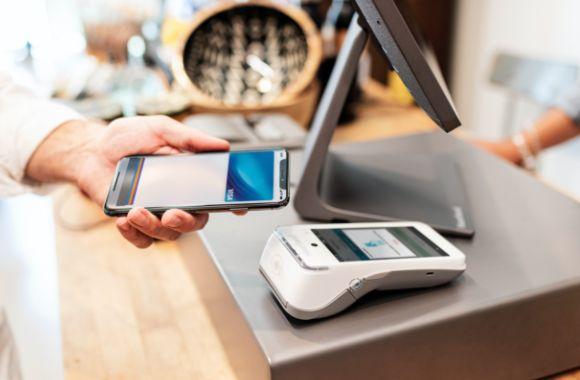 A customer making a payment via a mobile phone with mobile point of sale hardware