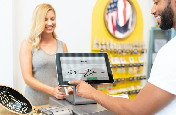 A customer signing on the point of sale and register interface