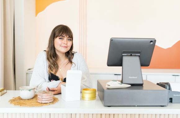 A retail worker sitting in front of point of sale and register machine