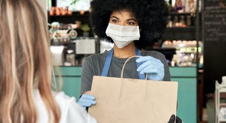 A store worker handing a bag to a customer