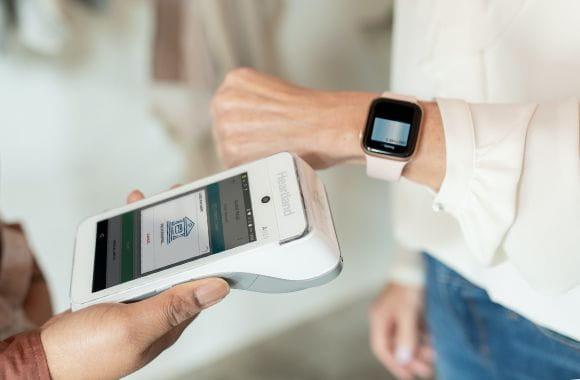 A customer making payment through a watch via a terminal