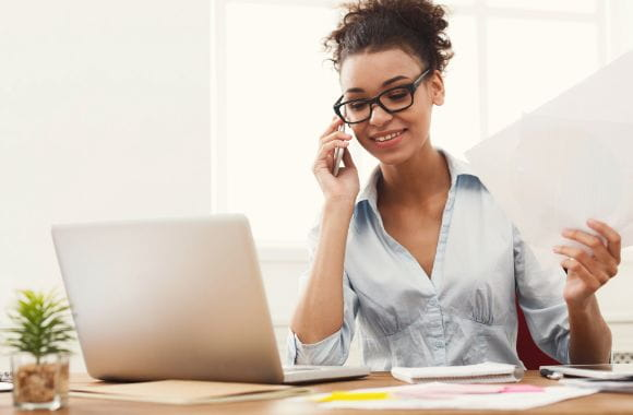 A women on the phone in front of her laptop