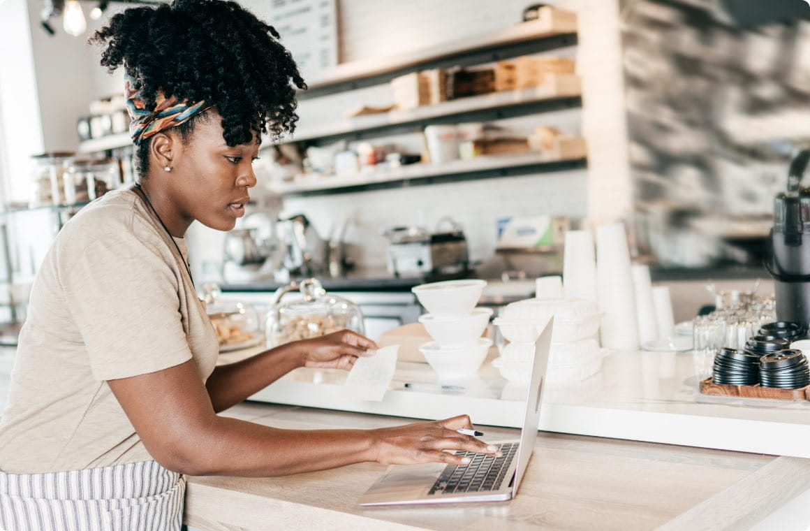 A woman managing a coffee shop business with a laptop