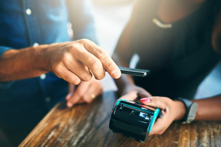 Person holding a cell phone over a contactless credit card reader