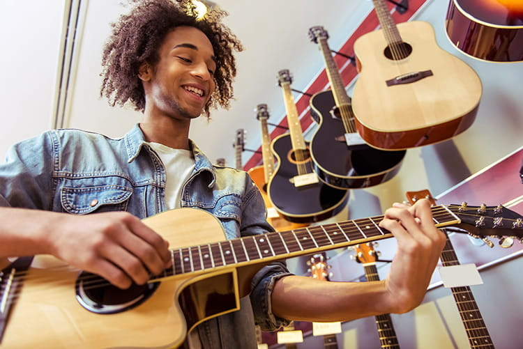 man playing guitar at a guitar retail location