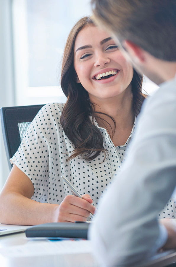 Woman laughing while working at desk and talking to man in office environment