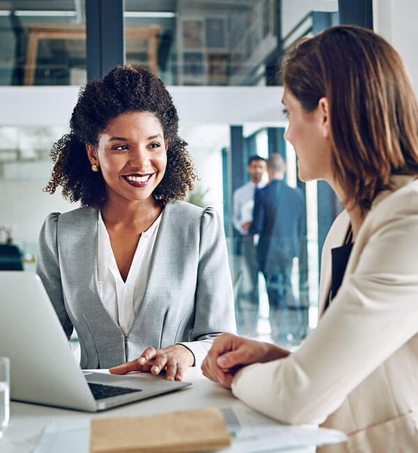 Woman smiling while using laptop at desk and talking to woman in office environment