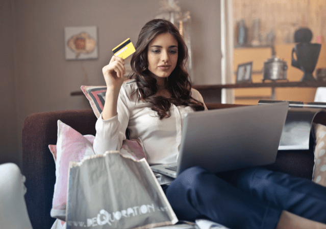 women making purchase with a credit card at her laptop