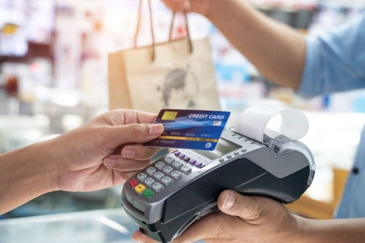 Shopper taps a contactless credit card to a card reader at a retail store