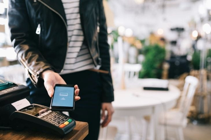 Man taps a smartphone to a contactless card reader at a restaurant