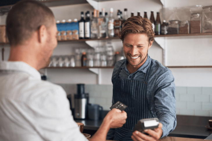 A man hands a credit card to a barista holding a card reader