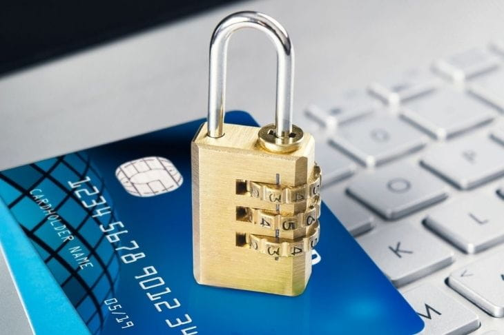 Padlock and credit card sitting on top of a computer keyboard