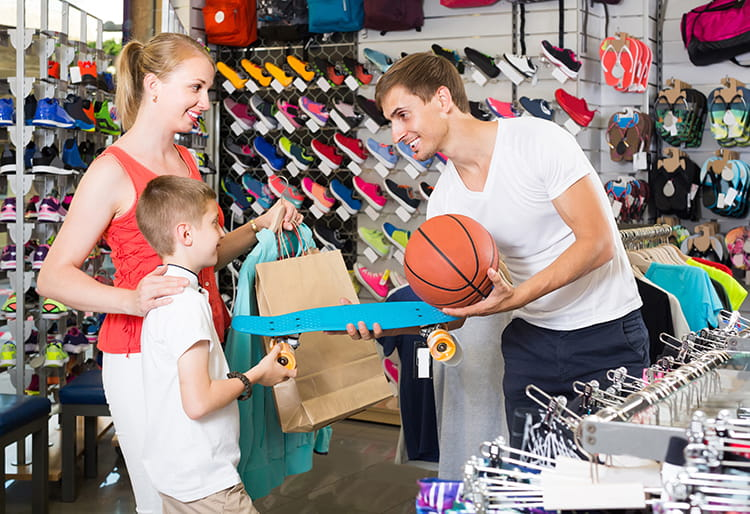 sports retail store with a mom and son being helped by man with basketball
