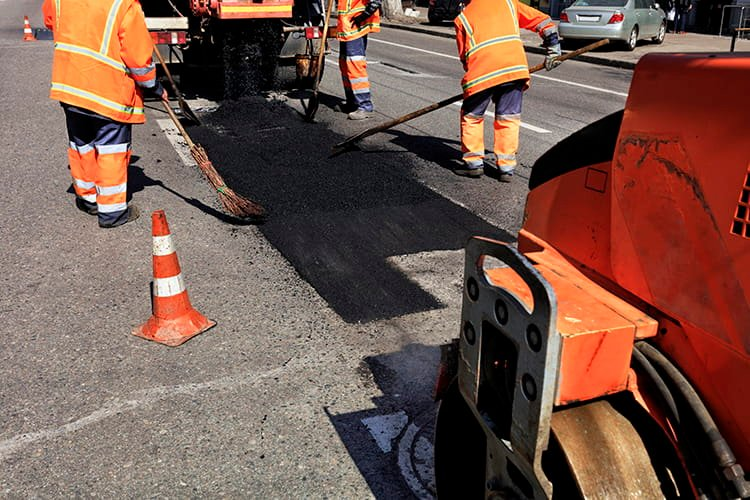 road workers laying asphalt with cones on the side of a road