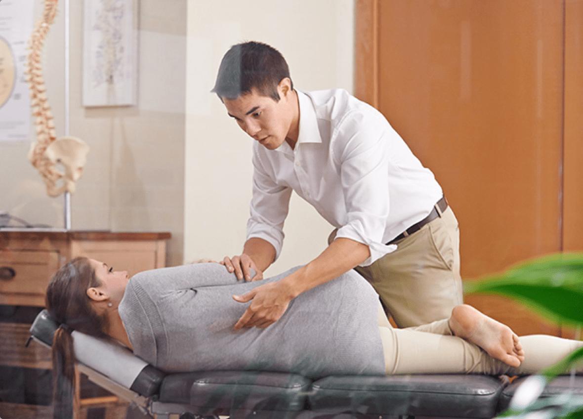 chiropractor adjusting patient back