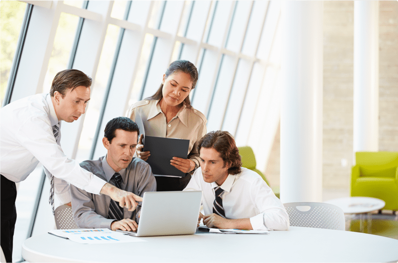 four professionals looking at a computer screen discussing PCI compliance