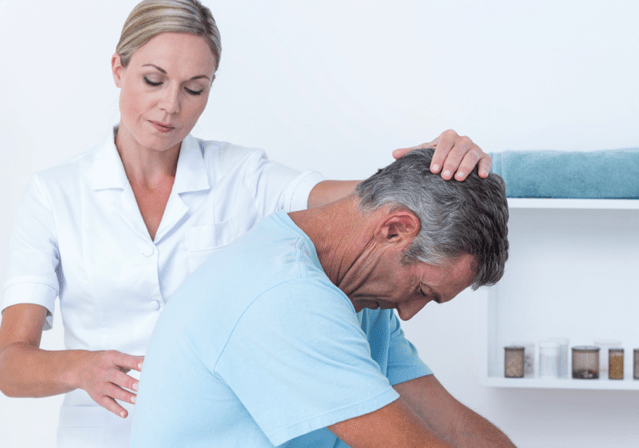 chiropractor adjusting a male patients spine