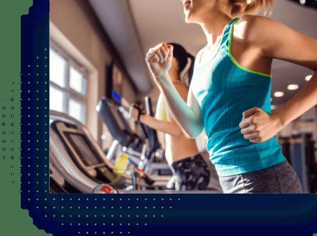 two women running on treadmills